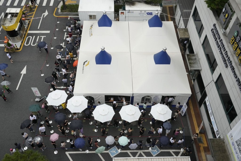 People queue in line to get coronavirus testing at a Public Health Center in Seoul, South Korea, Sunday, July 11, 2021. (AP Photo/Ahn Young-joon)