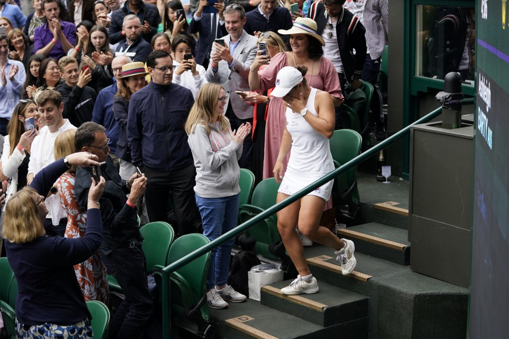 Australia's Ashleigh Barty walks back down the stands after climbing it to meet her team, at the end of her match against Czech Republic's Karolina Pl...