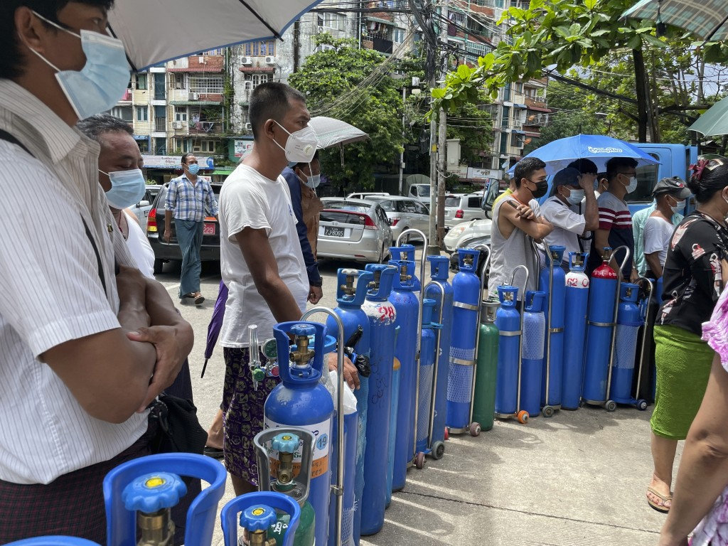 People queue up with their oxygen tanks outside an oxygen refill station in Pazundaung township in Yangon, Myanmar, Sunday, July 11, 2021. Myanmar is ...