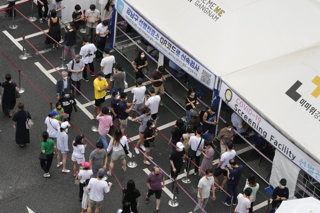 """People queue in line to wait to get coronavirus testing at a Public Health Center in Seoul, South Korea, Sunday, July 11, 2021. The banner reads: """"Qui..."""