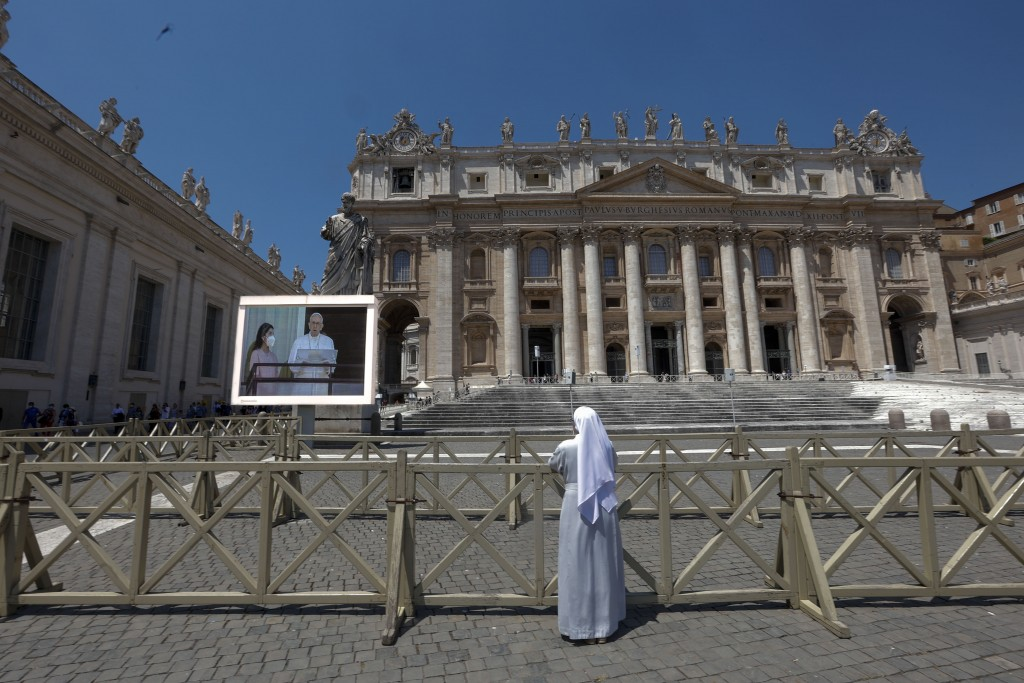 A nun watches, on a giant screen set up in St Peter's Square at the Vatican, Pope Francis as he appears on a balcony of the Agostino Gemelli Polyclini...