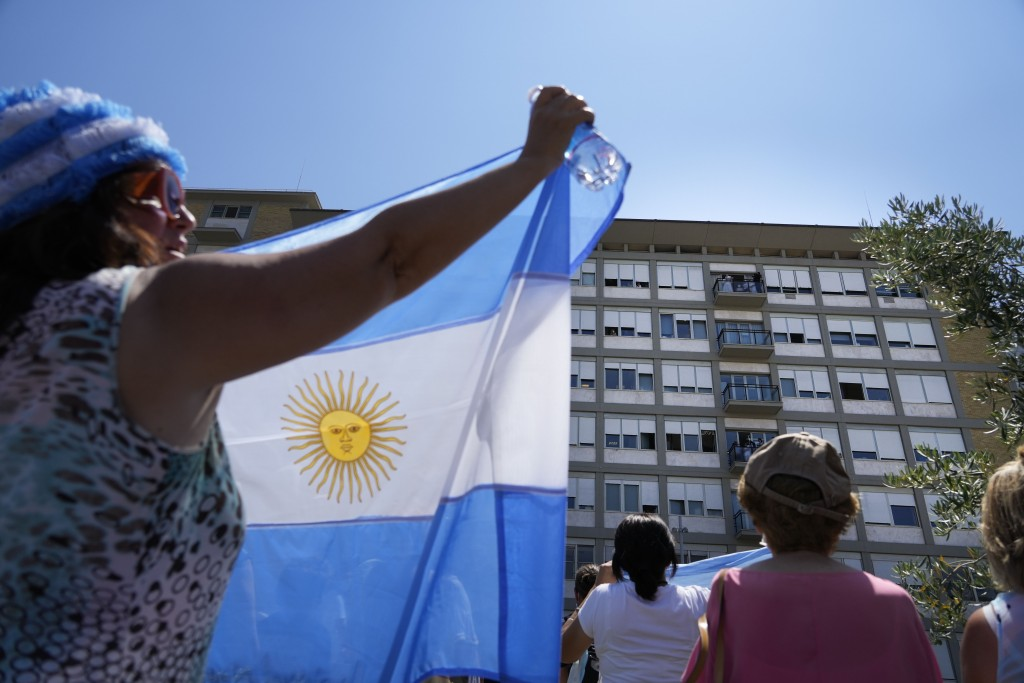 Faithful display Argentinian flags as they listen to Pope Francis standing on a balcony of the Agostino Gemelli Polyclinic in Rome, Sunday, July 11, 2...