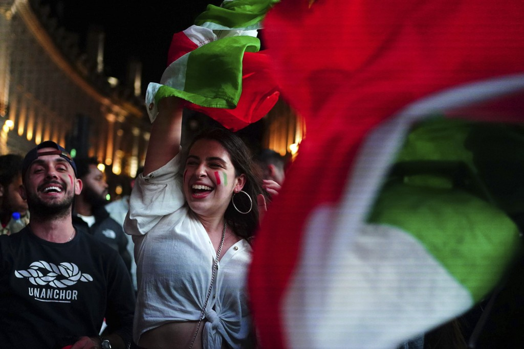 Italy fans celebrate in Piccadilly Circus in central London after their team won the UEFA Euro 2020 Final against England, Sunday July 11, 2021. (Vict...