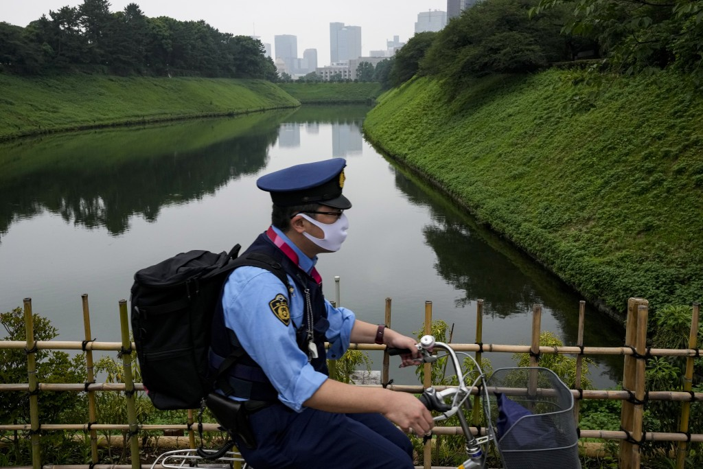 A police officer rides his bicycle along Imperial Palace Sunday, July 11, 2021, in Tokyo. The fourth state of emergency would go in effect on Monday a...