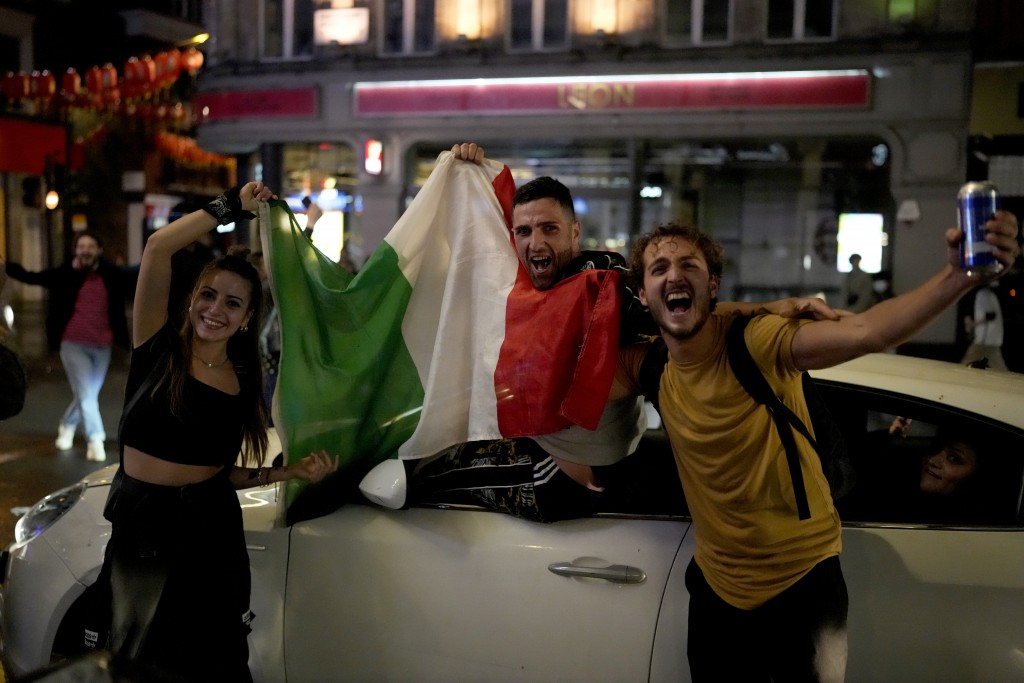 Italian fans celebrate in central London, in the early hours of Monday, July 12, 2021, after Italy won the Euro 2020 soccer championship final match b...