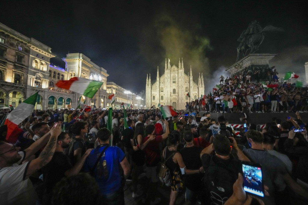 Italy's fans celebrate in front of the Duomo cathedral in Milan, Monday, July 12, 2021, after Italy beat England to win the Euro 2020 soccer champions...