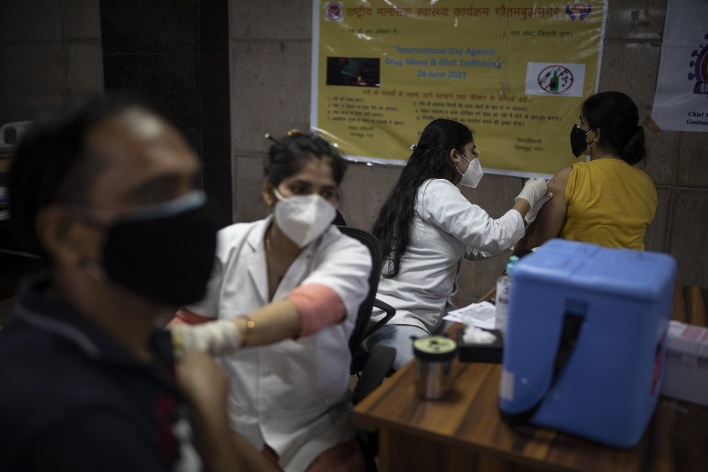 People receive Covishield vaccines against the coronavirus at a government hospital in Noida, a suburb of New Delhi, India, Monday, July 12, 2021. (AP...