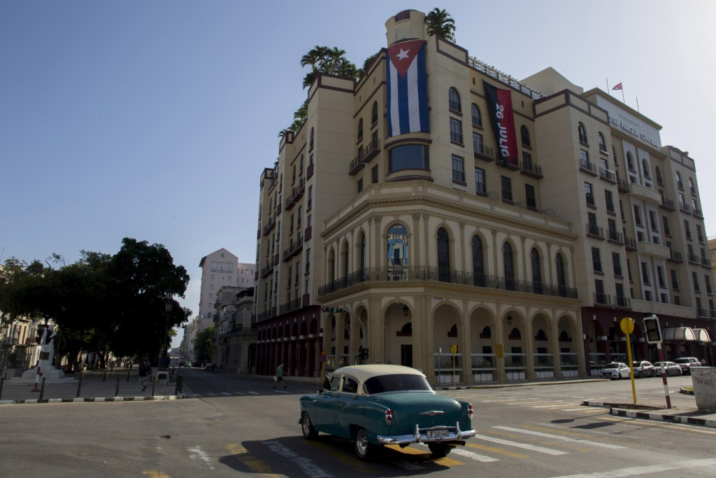 A Cuban flag hangs on Parque Central Hotel in Havana, Cuba, early Monday, July 12, 2021, the day after protests against food shortages and high prices...
