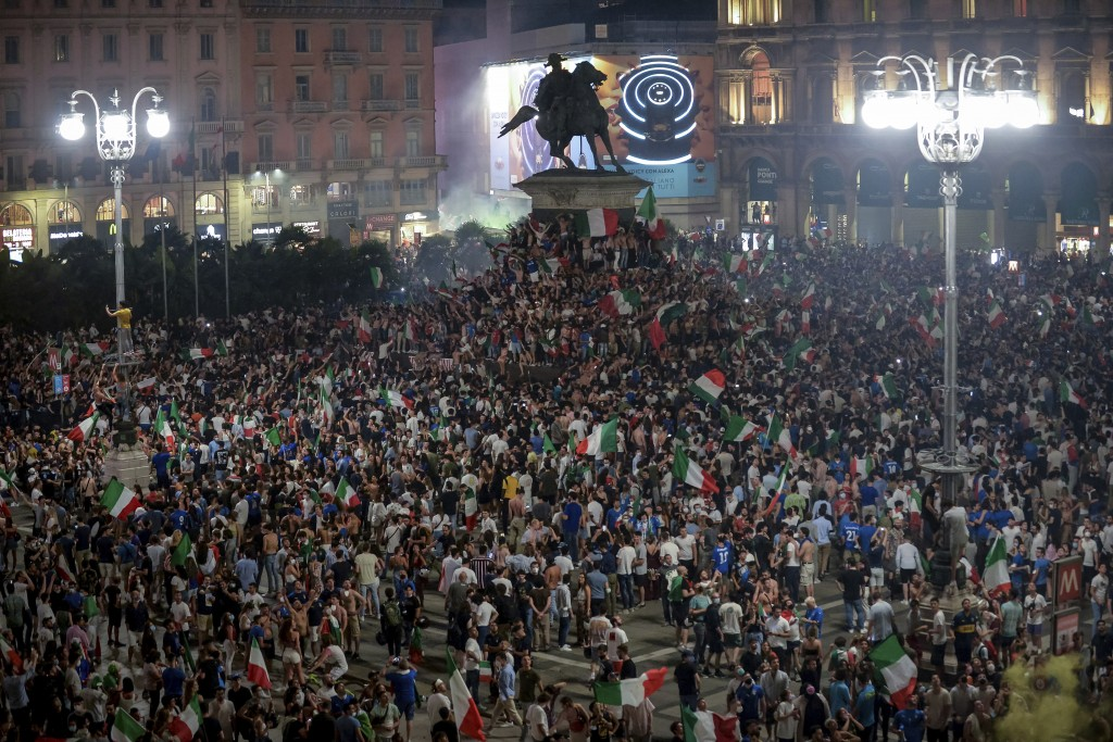 Fans celebrate in Piazza Duomo in Milan, Italy Sunday, July 11, 2021 after their team won the European Championship against England. Italy won the Eur...