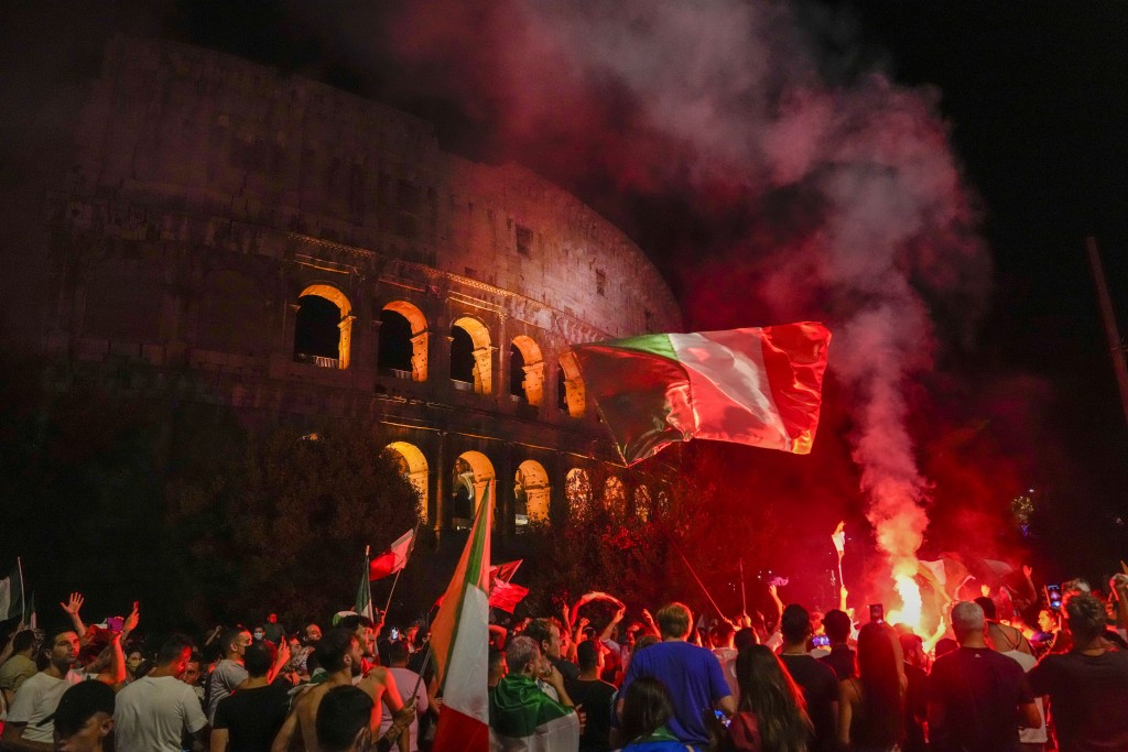 Italy's fans celebrate in front of the ancient Colosseum in Rome, Monday, July 12, 2021, after Italy beat England to win the Euro 2020 soccer champion...