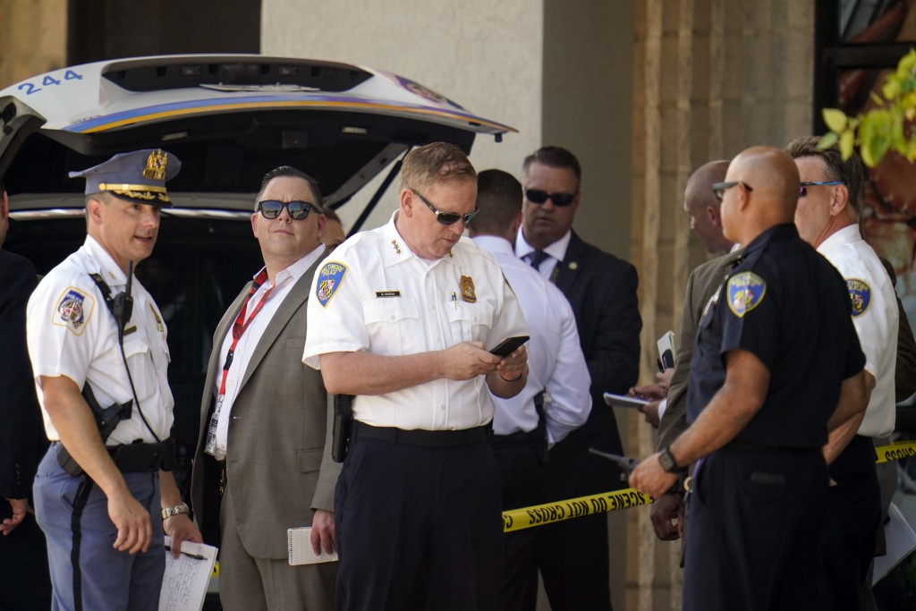 Law enforcement officials gather near a mall parking area where two Baltimore city police officers were shot and a suspect was killed as a U.S. Marsha...