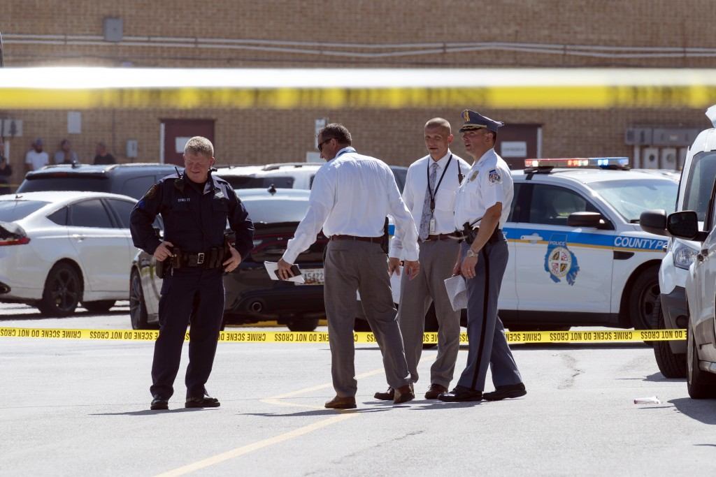 Law enforcement officials confer near a mall parking area where two Baltimore city police officers were shot and a suspect was killed as a U.S. Marsha...