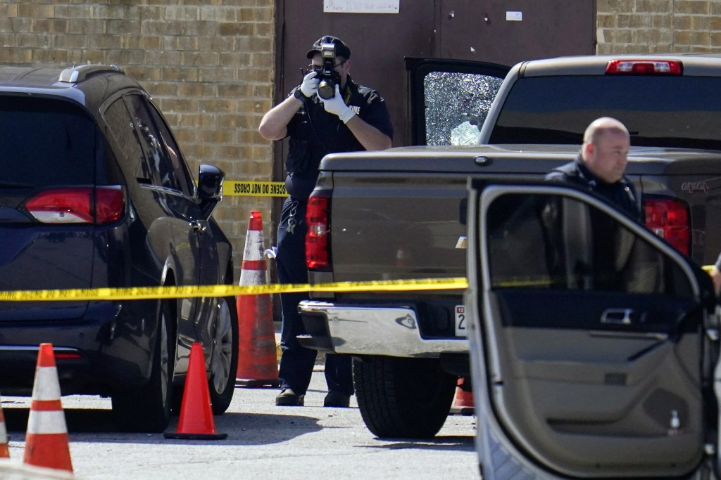Shattered glass is seen on a pickup's driver side door as investigators document the scene in a mall parking area where two Baltimore city police offi...