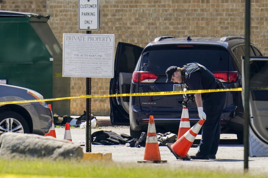 Body armor is seen near a minivan as a forensics worker inspects an area where two officers on the U.S. Marshals' task force were allegedly shot in Ba...
