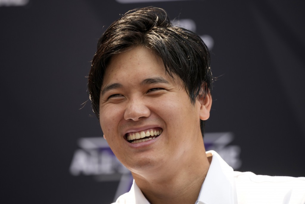 Shohei Ohtani, of the Los Angeles Angeles, laughs after being named the American League's starting pitcher for the MLB All-Star baseball game, Monday,...
