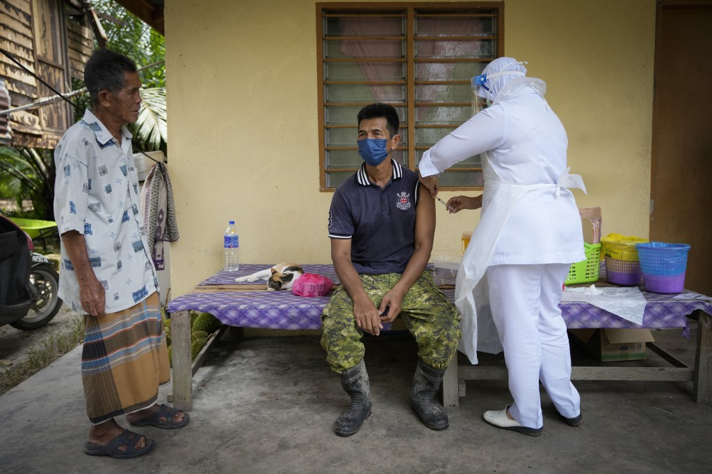 A nurse administers a Pfizer COVID-19 vaccine to a farmer outside his home in rural Sabab Bernam, central Selangor state, Malaysia, Tuesday, July 13, ...