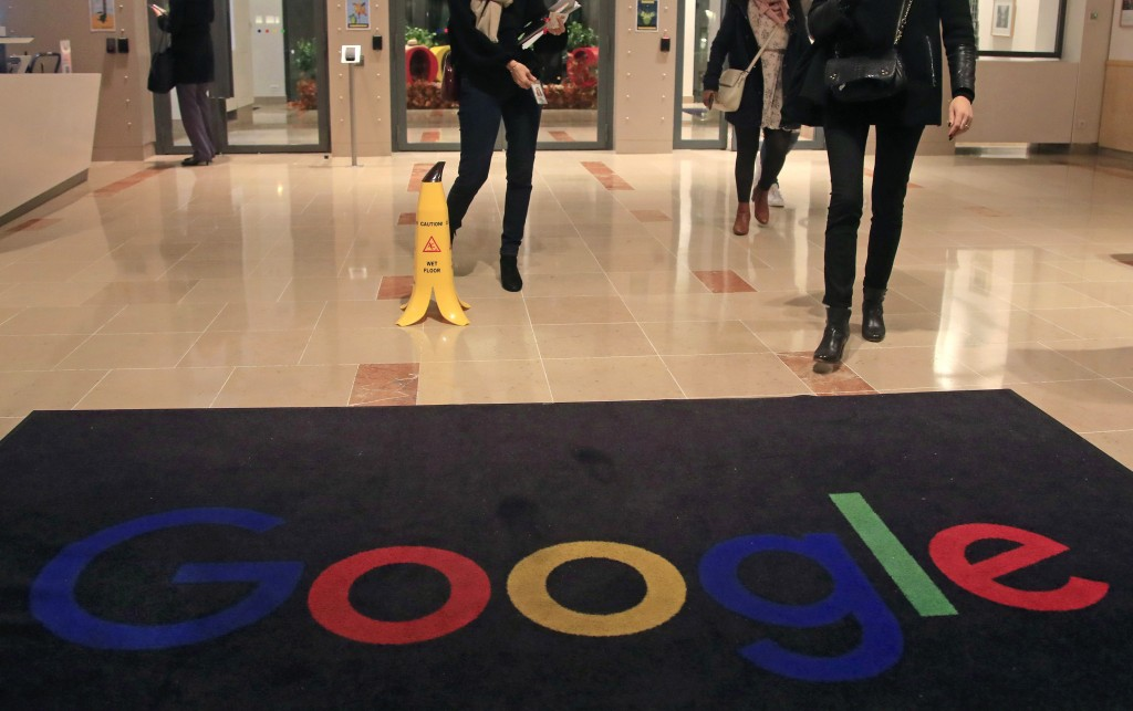 FILE - In this file photo dated Nov. 18, 2019, Google employees walk out of Google France building in Paris. France's competition regulator said Tuesd...
