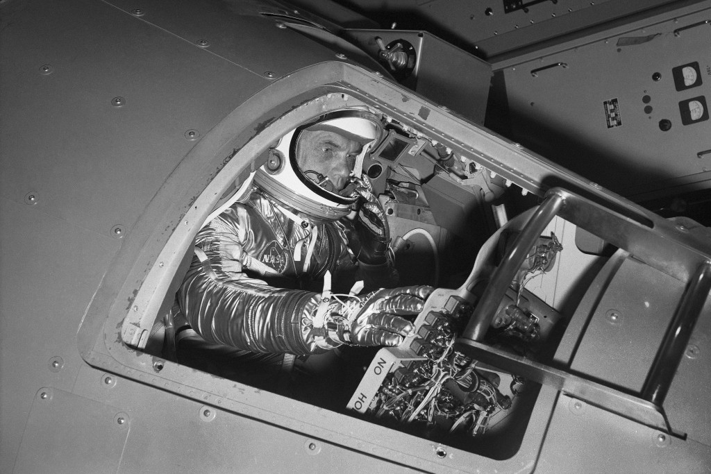 FILE - In this Jan. 11, 1961 file photo, then Marine Lt. Col. John Glenn reaches for controls inside a Mercury capsule procedures trainer as he shows ...
