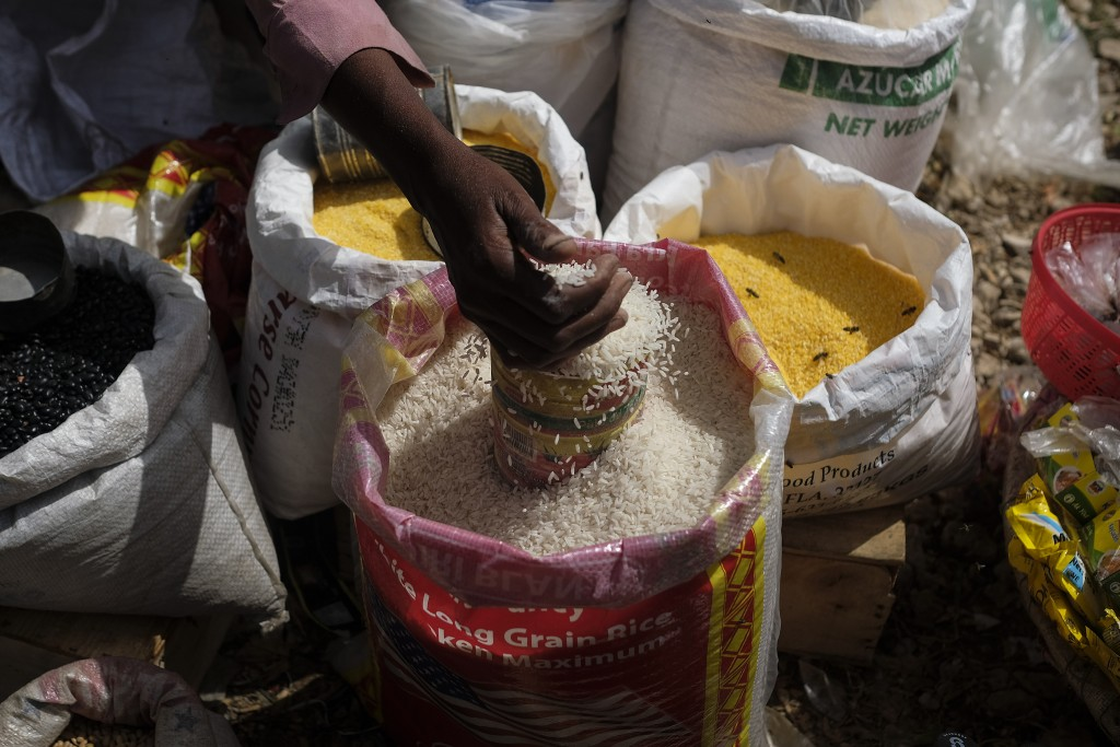 A rice vender fills a container at the Maché Tèt Dlo market in Port-au-Prince, Haiti, Tuesday, July 13, 2021. President Jovenel Moise was assassinated...