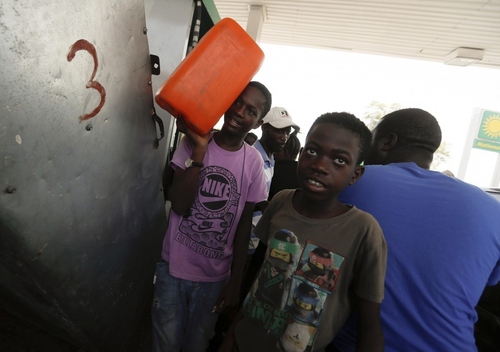 A boy carries a tank of gas as he leaves a gas station in Port-au-Prince, Tuesday, July 13, 2021, almost a week after President Jovenel Moise was assa...