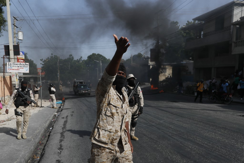 Police clear burning tire road blocks set by protesters upset with growing violence in the Lalue neighborhood of Port-au-Prince, Haiti, Wednesday, Jul...