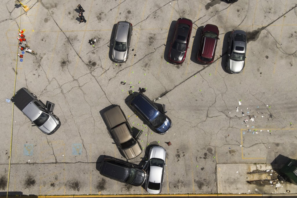 Officials inspect an area in the parking lot of a mall where two officers on the US Marshals' task force were allegedly shot in Baltimore, Tuesday, Ju...