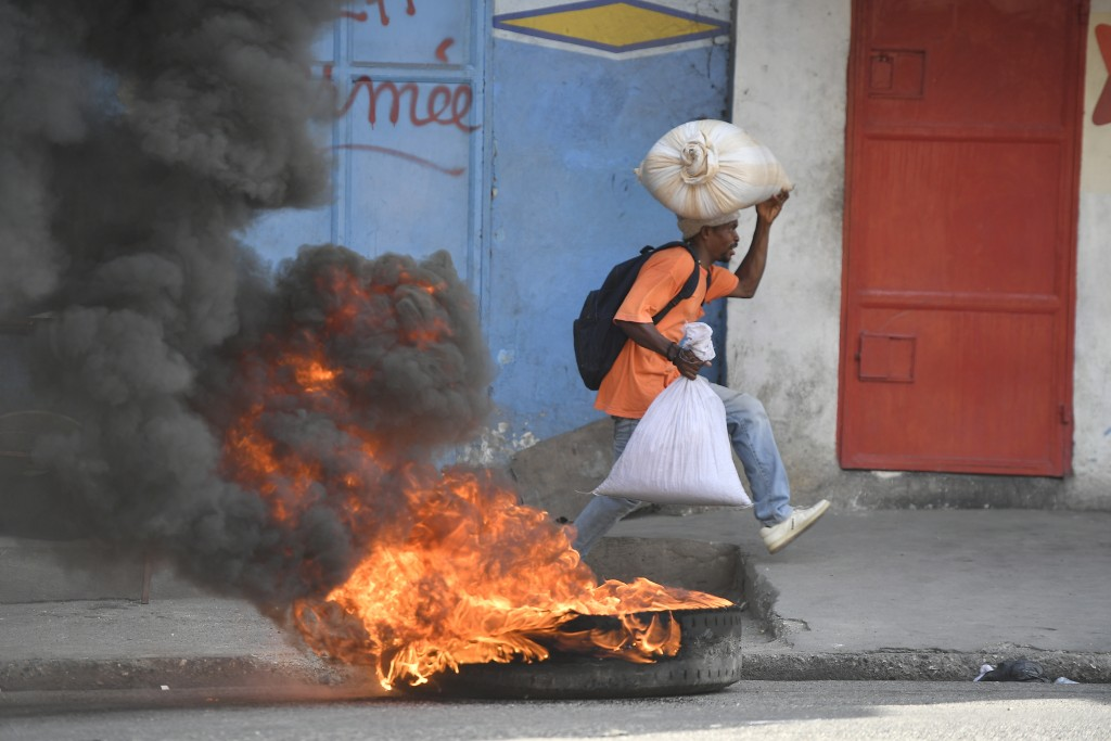 A man runs past a tire set on fire by protesters upset with growing violence in the Lalue neighborhood of Port-au-Prince, Haiti, Wednesday, July 14, 2...