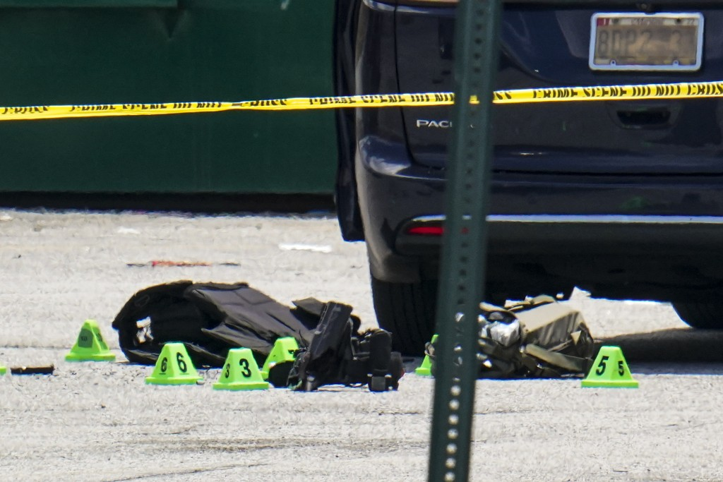 Body armor and evidence markers rest on the tarmac by a minivan near a mall parking area where two Baltimore city police officers were shot and a susp...