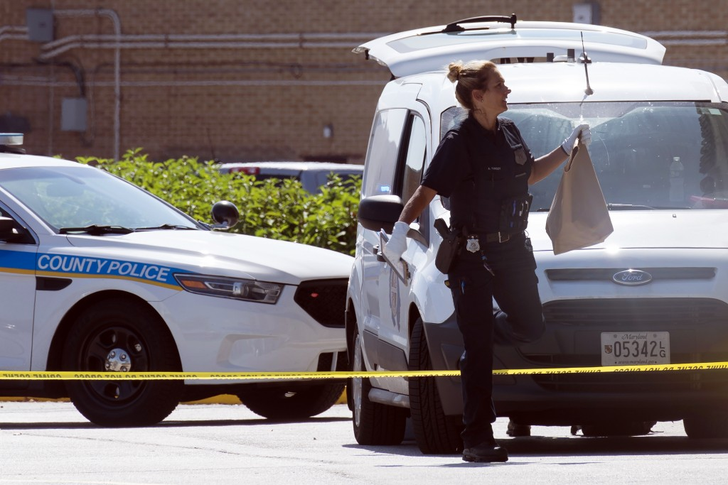 A Baltimore police forensic service officer carries a bag in an area where two Baltimore city police officers were shot and a suspect was killed as a ...