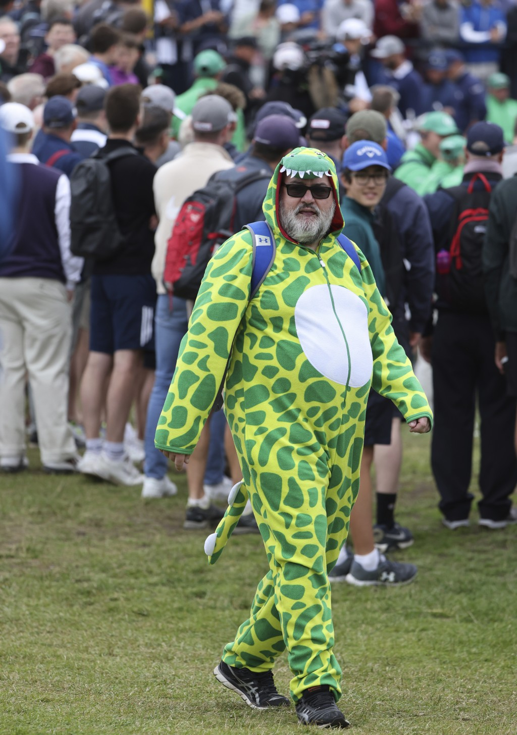 A gold fan dress as a dinosaur joins the crowd watch a practice round for the British Open Golf Championship at Royal St George's golf course Sandwich...