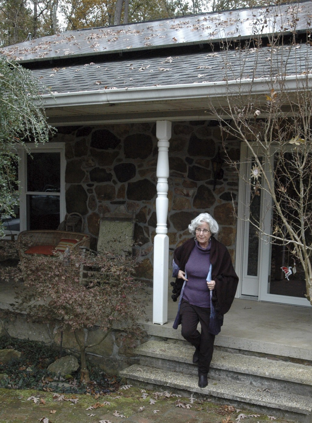 FILE - In this Thursday, Nov. 14, 2019 file photo, Teresa Thorne walks out of her solar power-equipped home near Springville, Ala. The fees imposed by...