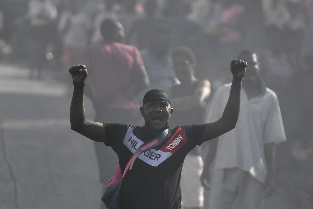 A man protests against growing violence amid smoke from tires set fire by demonstrators in the Lalue neighborhood of Port-au-Prince, Haiti, Wednesday,...