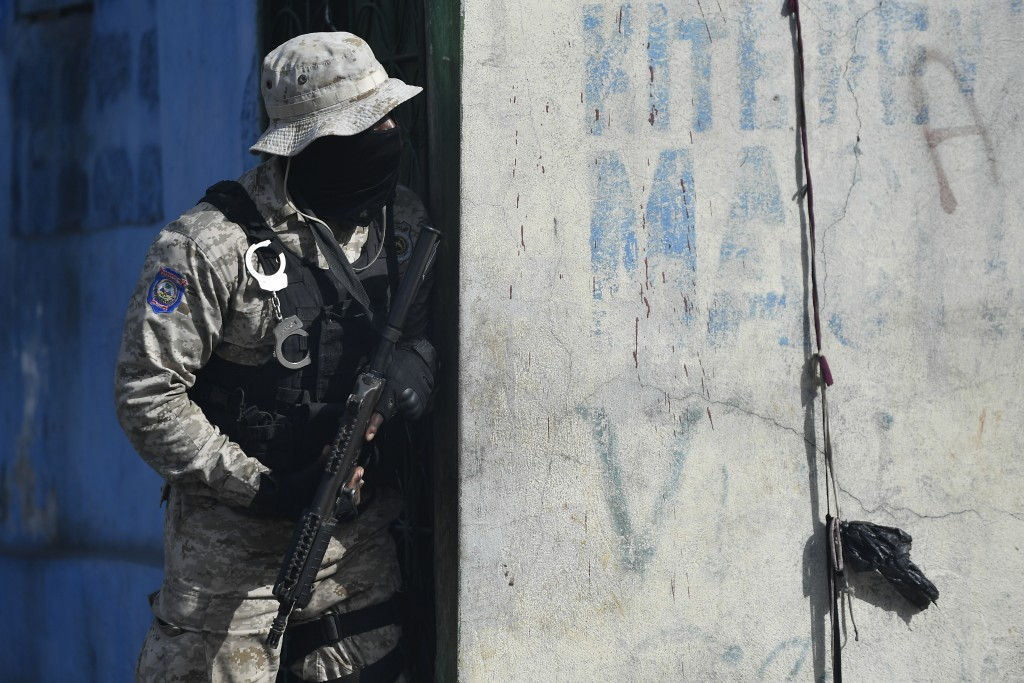 A police officer watches protests by residents in the Lalue neighborhood who are upset with growing violence in Port-au-Prince, Haiti, Wednesday, July...