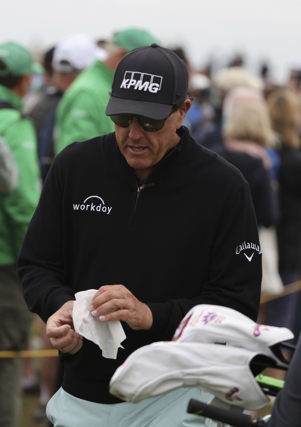 United States' Phil Mickelson wipes his hands after throwing back a fans ball that that had been offered for him to sign as he walks to the 3rd tee du...
