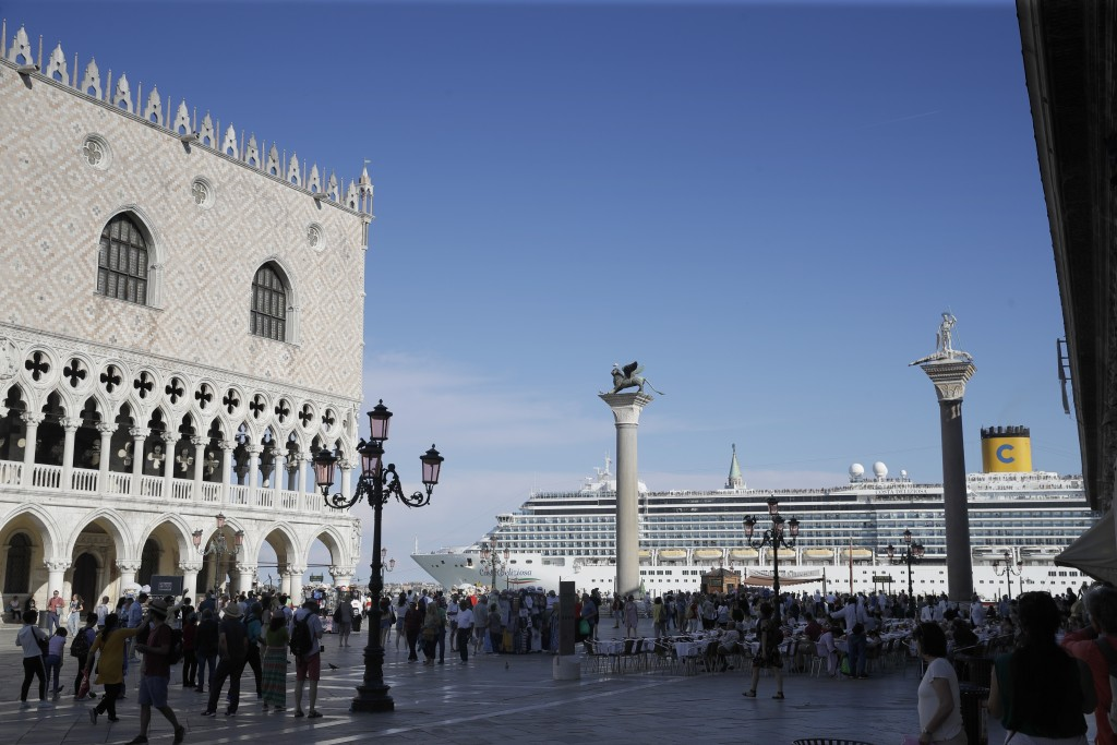 """FILE-- A cruise ship passes by St. Mark's Square in Venice, Italy, Sunday, June 2, 2019. Declaring Venice's waterways a """"national monument,"""" Italy is ..."""