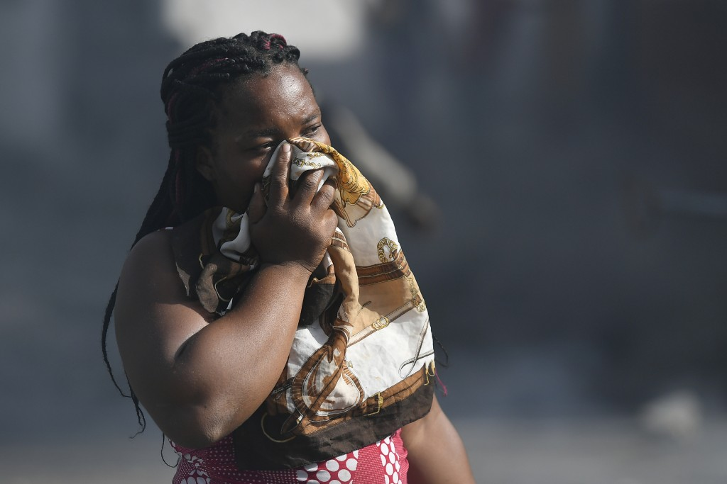 A woman covers her mouth as she walks through smoke from burning tires set fire by protesters upset with growing violence in the Lalue neighborhood of...
