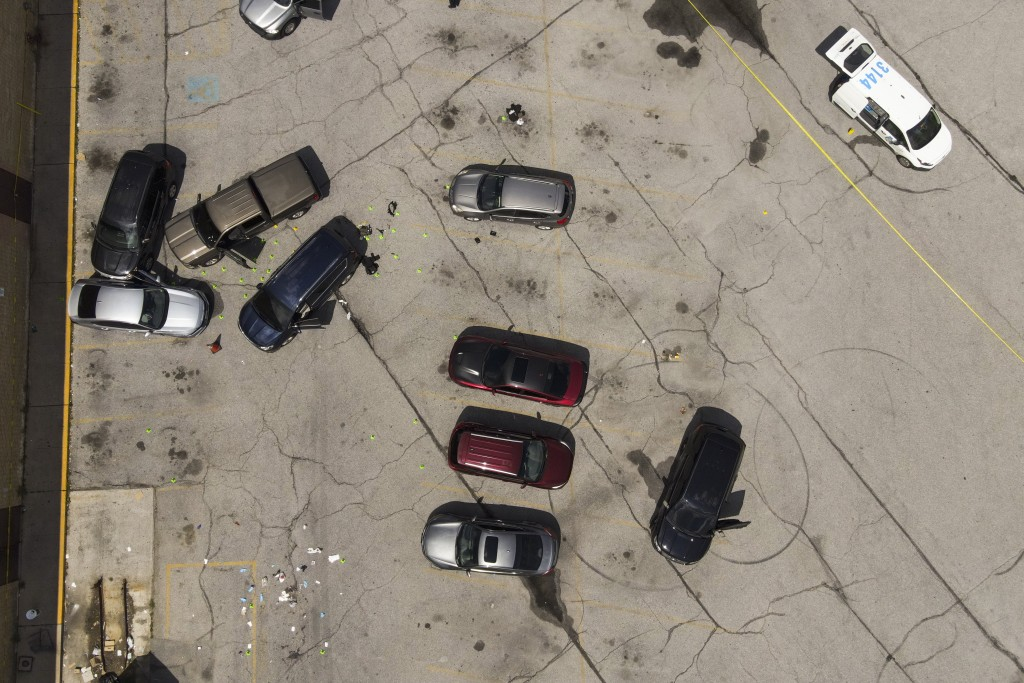 Officials inspect an area in the parking lot of a mall where two officers on the US Marshals' task force were allegedly shot in Baltimore, according t...