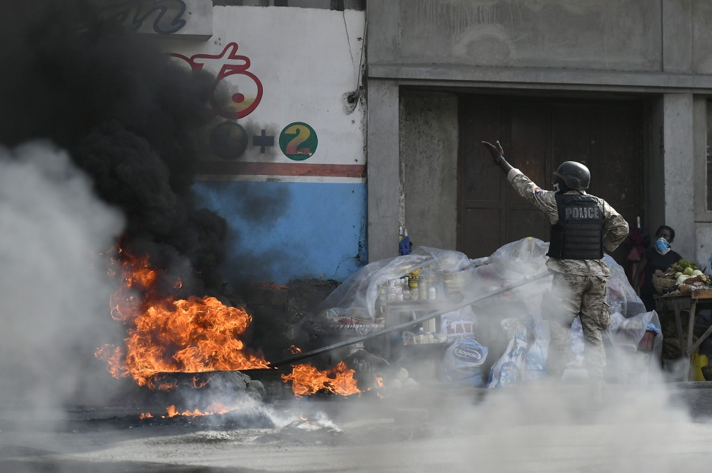 A police officer pushes a burning tire to the side of the road so cars can pass, as people protest growing violence in the Lalue neighborhood of Port-...