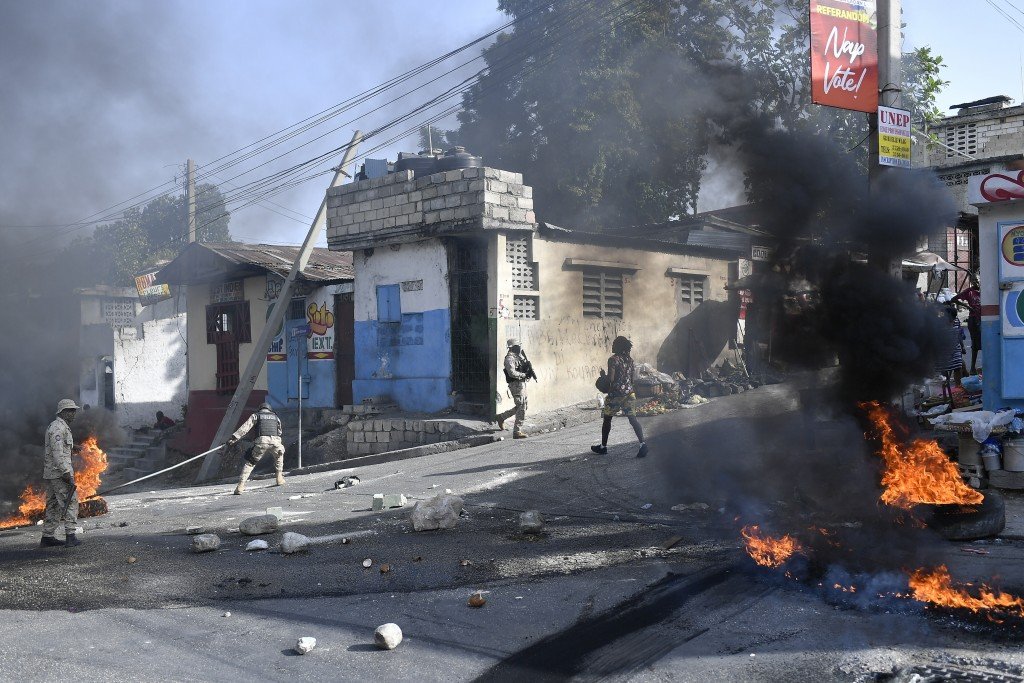 Tires burn after being set on fire by protesters upset with growing violence as police patrol and try to put out the flames and clear the road for veh...