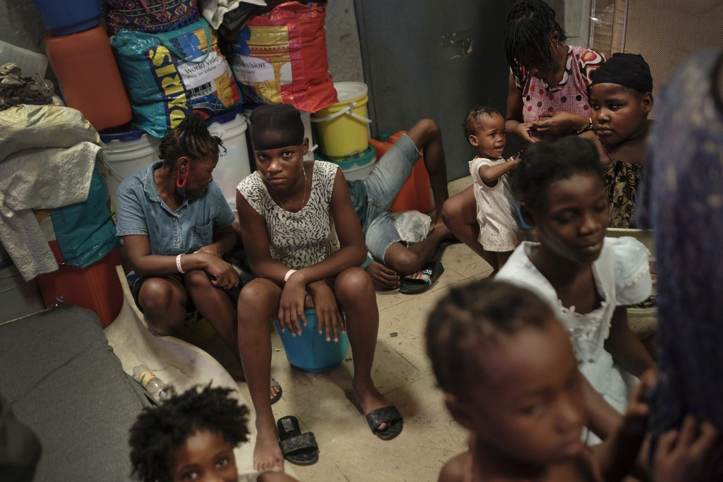 A youth looks into the camera inside a school turned shelter created about a month ago for families displaced by gang violence in Petion Ville in Port...