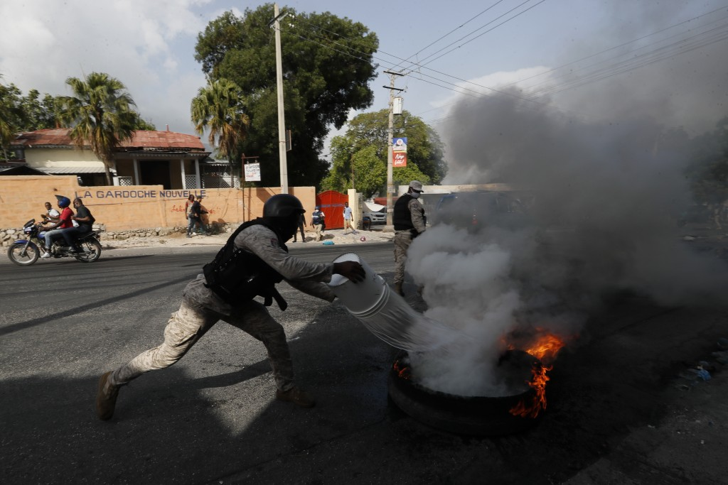 Police put out a burning tire set fire by protesters upset with growing violence in the Lalue neighborhood of Port-au-Prince, Haiti, Wednesday, July 1...