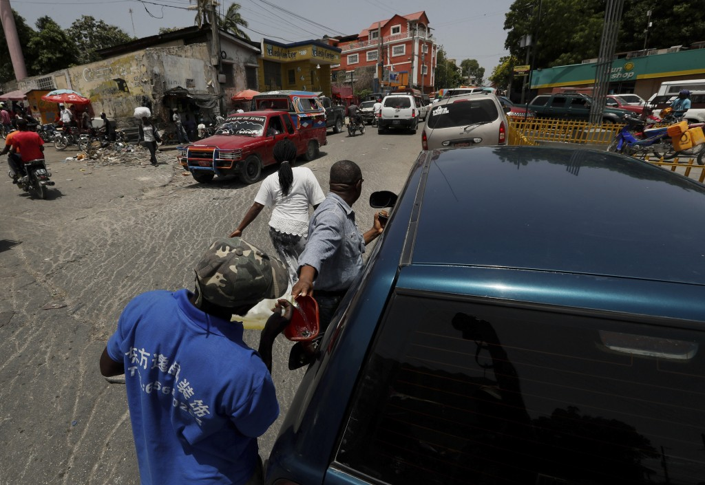 A young man fills a driver's tank with gasafter reselling it to him, in Port-au-Prince, Tuesday, July 13, 2021, almost a week after President Jovenel ...