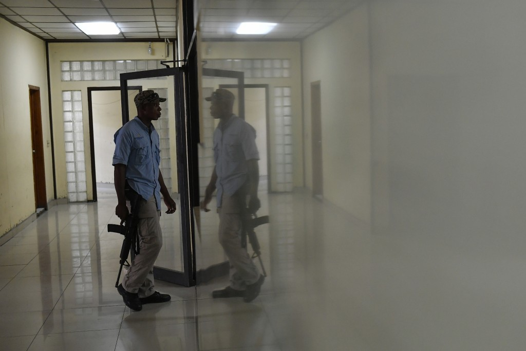 A bodyguard stands outside the prosecutors office that is investigating the assassination of President Jovenel Moise inside the courthouse in Port-au-...