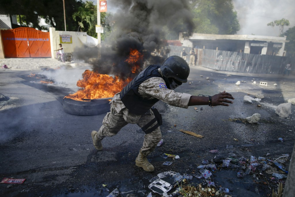 Police clear barricades of burning tires set by protesters upset with growing violence in the Lalue neighborhood of Port-au-Prince, Haiti, Wednesday, ...