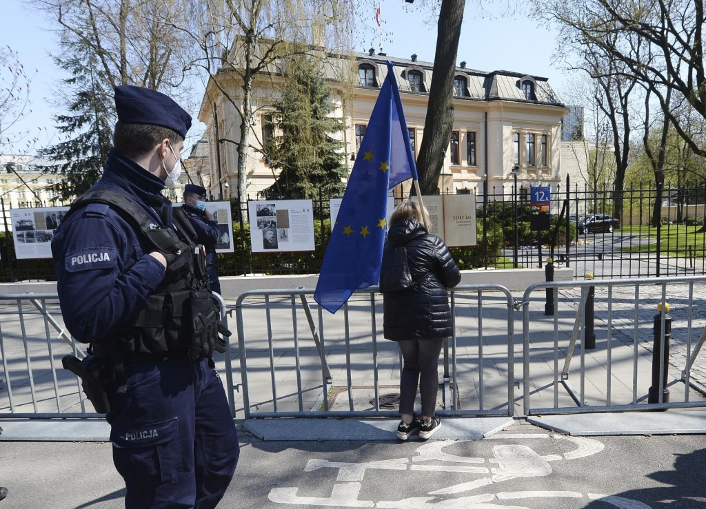 FILE - In this file photo dated Wednesday April 28, 2021, a woman holds a European Union flag outside the Constitutional Tribunal, background, in Wars...
