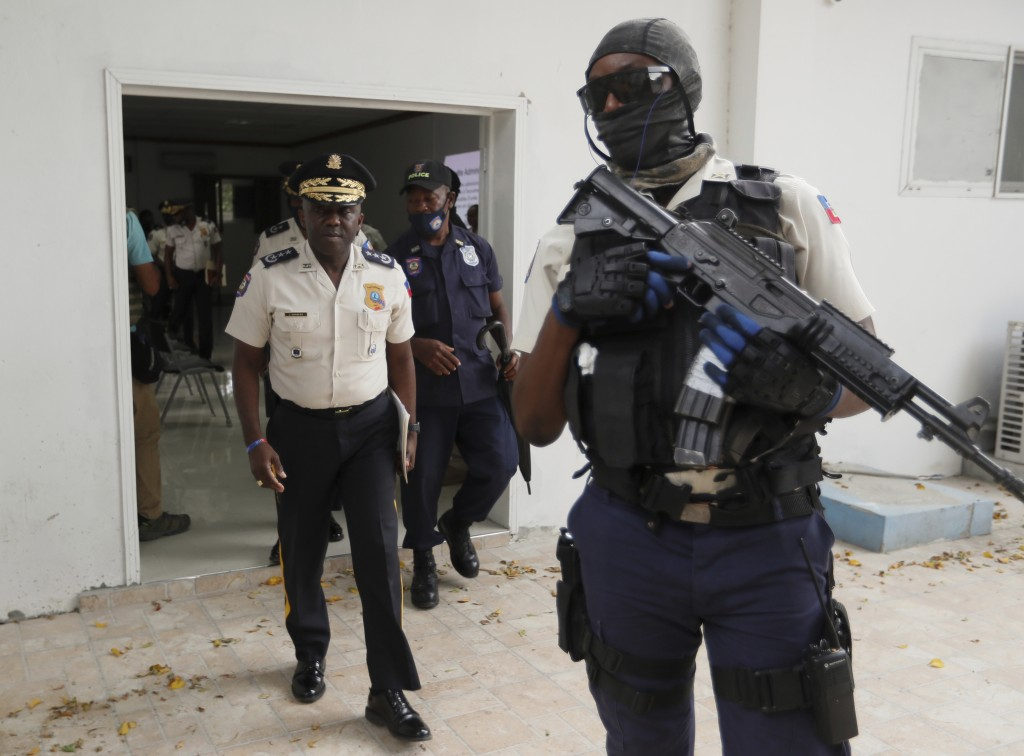 Leon Charles, left, Director General of Haiti's Police leaves a room after a news conference at police headquarters in Port-au-Prince, Wednesday, July...