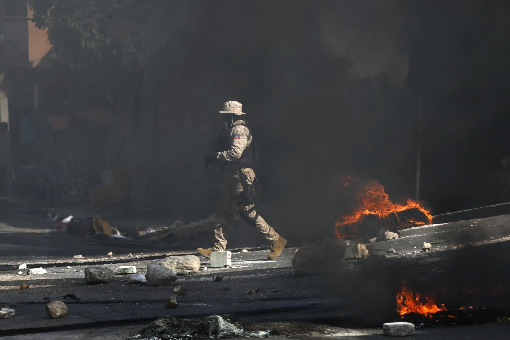 Police work to clear a road blocked by rocks and tires set fire by protesters upset with growing violence in the Lalue neighborhood of Port-au-Prince,...