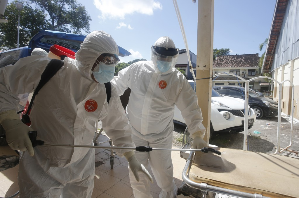 Health workers in protective suits spray disinfectant after carrying the body of a COVID-19 victim in Denpasar, Bali, Indonesia on Thursday, July 15, ...
