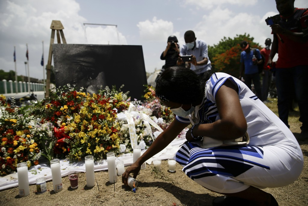 A woman lights a candle at a memorial outside the Presidential Palace in memory of slain President Jovenel Moise in Port-au-Prince, Haiti, Wednesday, ...
