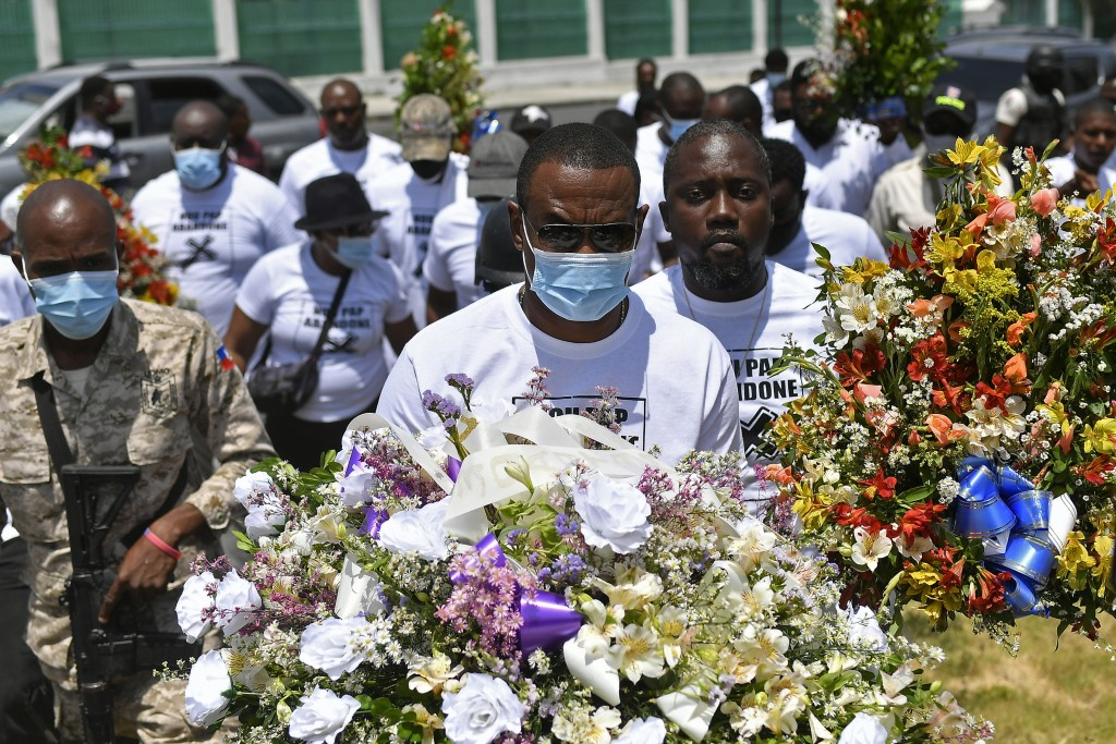Pierre Gary Bernadotte, a member of the slain president's PHTK political party, carries flowers to a spot outside the presidential palace in memory of...